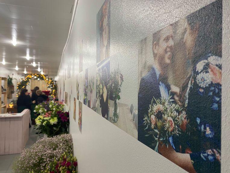 Op een muur zijn foto's geprint, van gehuwde mensen met een boeketje van Seda.
