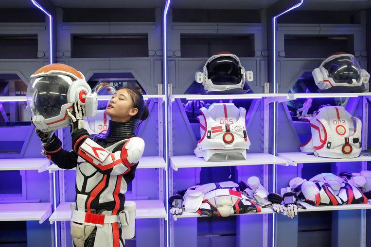Een medewerker van de Marssimulator toont hoe je het best de helm van een ruimtepak opzet. Beeld REUTERS