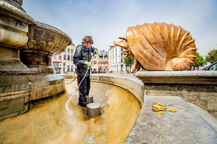 Marco Bakker van Marco4service maakt de filters schoon bij de Wilhelminafontein op de Brink. Het geld dat hij vindt laat hij liggen voor mensen die het harder nodig hebben.