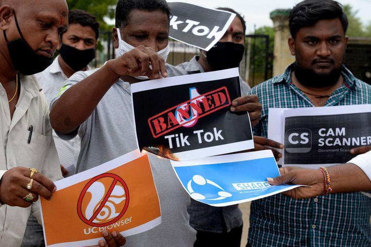 Leden van een jeugdorganisatie van de stad Hyderabad tonen posters waarmee ze hun steun betuigen voor de beslissing TikTok in India te verbieden.  Beeld AFP