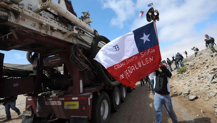 Familieleden van de mijnwerkers juichen de vrachtwagen met de boor toe Beeld afp