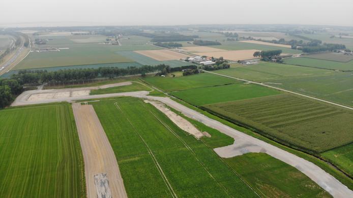 De weg van staalslakken die in de polder is aangelegd. Achterin is het depot waar baggerspecie in gestort zou moeten worden. Daarnaast Cora van Mook.