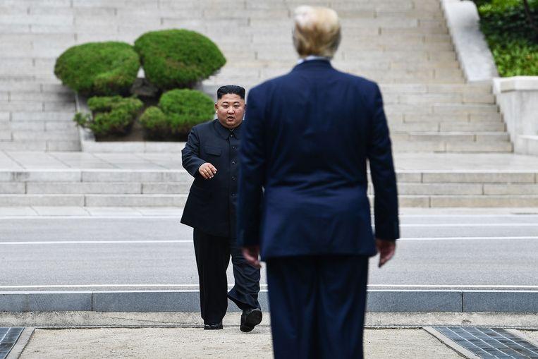 De Noord-Koreaanse leider Kim Jong-un loopt de Amerikaanse president Donald Trump tegemoet bij de demarcatielijn tussen Noord-Korea en Zuid-Korea, 30 juni 2019. Beeld AFP