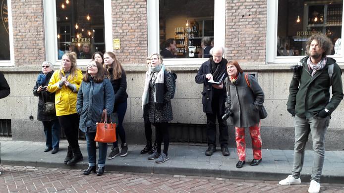 Het groepje van de Stadsbibliotheek Den Bosch bekijkt de gedichten op de Bossche gevels.