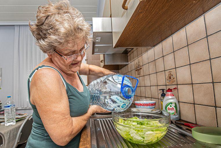 Hélène Debeyne wast haar sla met het  nooddrinkwater dat wordt uitgedeeld aan de getroffen bewoners.