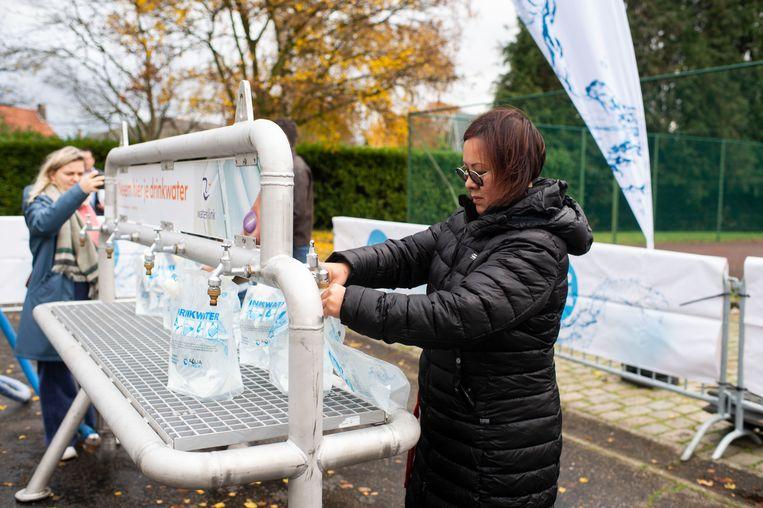Een vrouw tapt water van de noodinstallatie. Elke inwoner heeft bij problemen met het drinkwater recht op 3 liter per dag, een huisdier heeft recht op 1 liter.