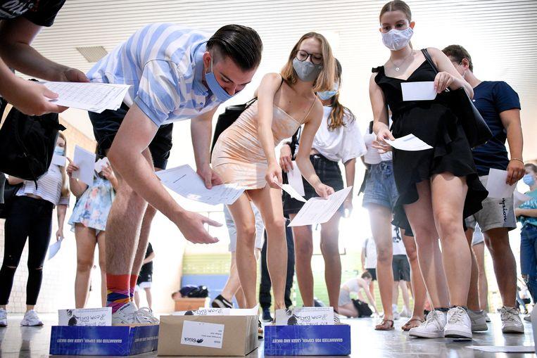Scholieren in het Duitse Duisburg melden zich aan in de gymzaal, mét mondkapje.  Beeld EPA