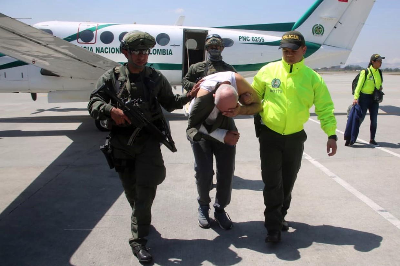 Saïd R. tussen twee leden van het Colombiaanse arrestatieteam in. Beeld EPA