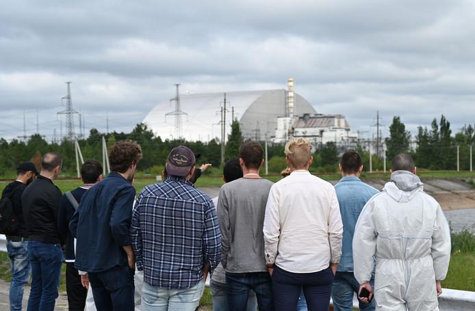 Des touristes contemplent l'arche de Tchernobyl, un dispositif de confinement du réacteur 4 accidenté de la centrale nucléaire.