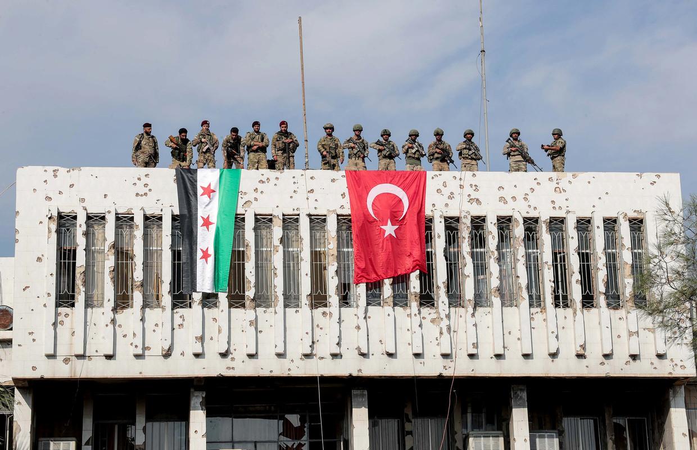 Turkse militairen (rechts) en Syrische strijders die met hen meevechten op een gebouw in de grensplaats Ras al-Ain, waar ze de Koerden hebben verdreven.