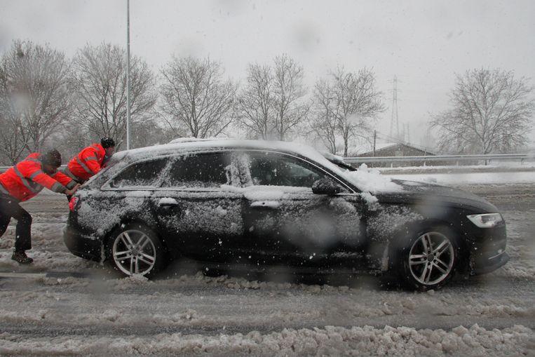 Marnix Olivier en Filip Holvoet van de technische dienst van de stad Roeselare helpen een vastgereden auto weer op weg.