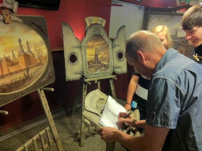 Bezoekers tekenen het gastenboek.