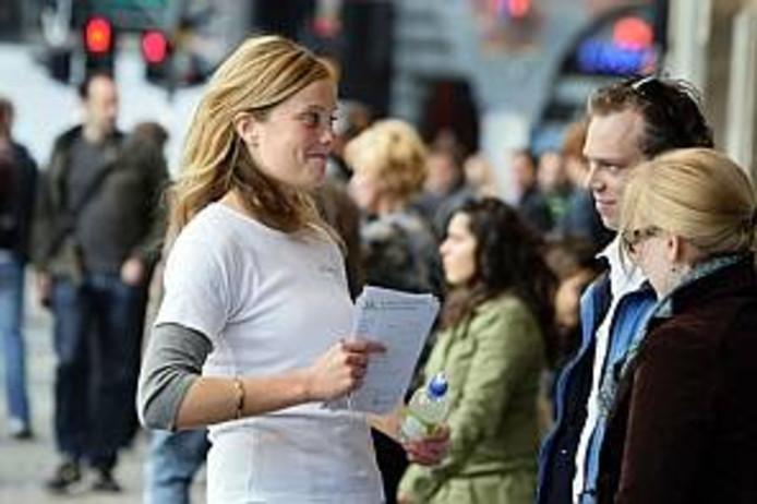 Een straatverkoopster spreekt winkelend publiek aan.