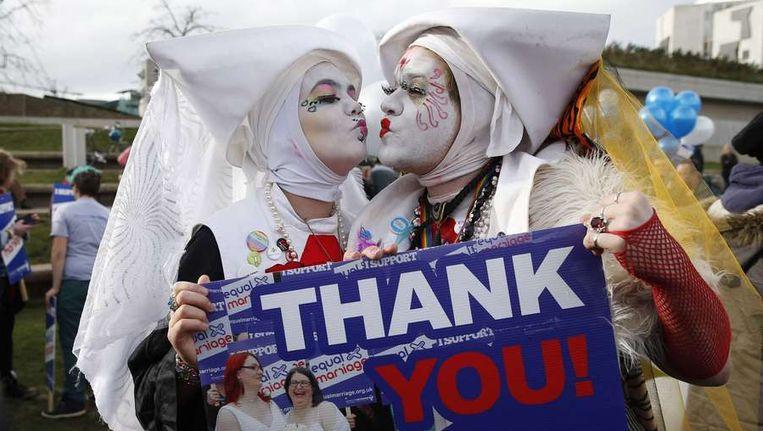 Aanhangers van het homohuwelijk tonen hun blijdschap voor de deur van het Schotse parlement, dinsdag. Beeld null