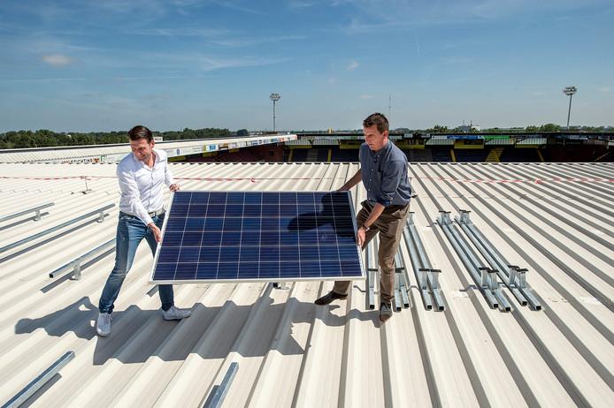 Juni 2018: wethouder Paul de Beer (r) en nac-directeur Justin Goetzee plaatsen symbolisch een eerste zonnepaneel op het dak van het NAC-stadion.