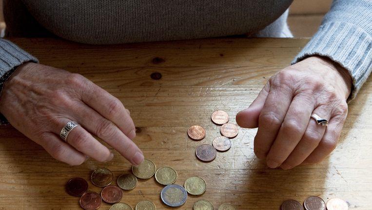 Gepensioneerde telt muntjes. De pensioenuitkeringen dreigen volgend jaar verlaagd te worden. Beeld ANP
