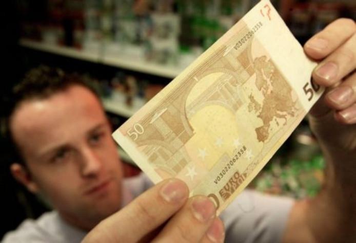 Een man beoordeelt de echtheid van een 50-eurobiljet.