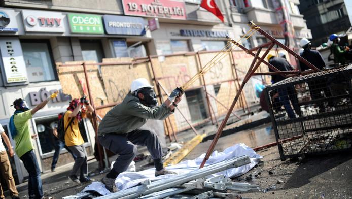 Een demonstrant schiet met een kattapult op de politie