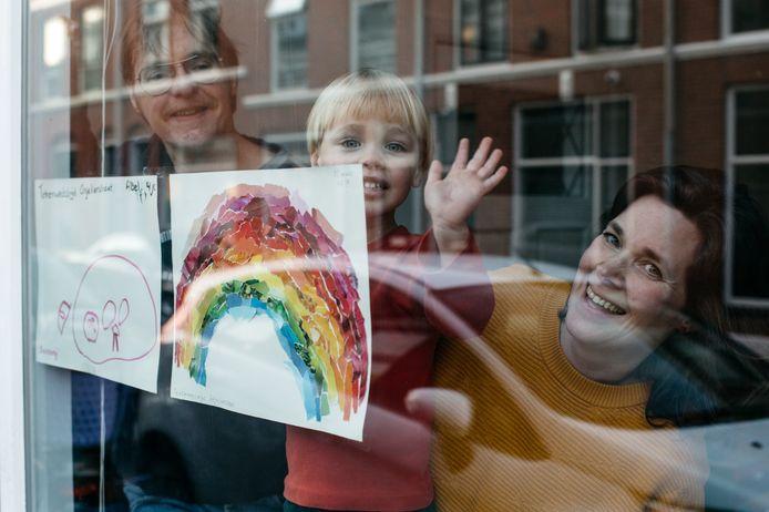 Abel (4) en zijn ouders Eelke en Maud achter het raam mét tekeningen in de Anjelierstraat in Utrecht.