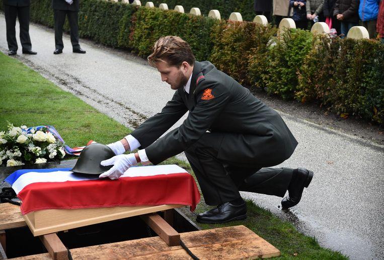Een oude helm wordt voor de ceremonie op de kist gelegd. Beeld Marcel van den Bergh