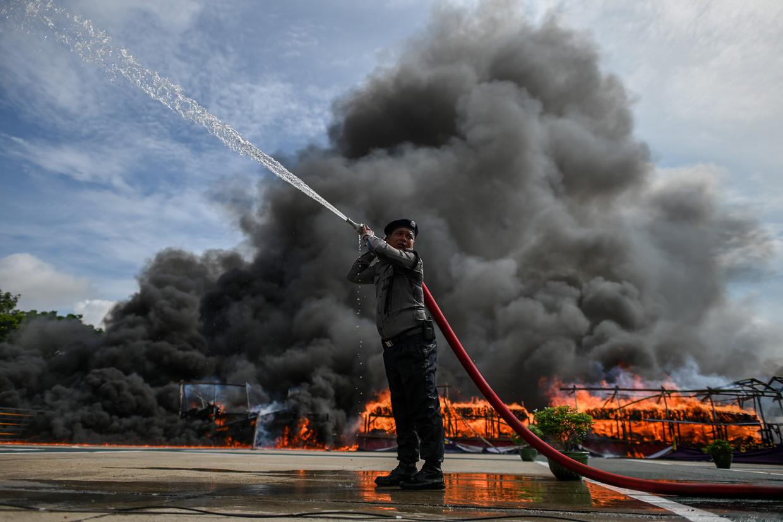 Een brandweerman in de Myanmarese stad Rangoon houdt het vuur onder controle van een enorme berg drugs die wordt vernietigd.
