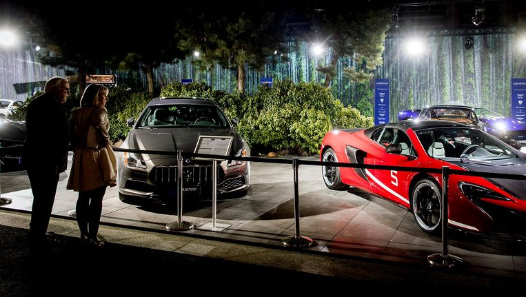 Bezoekers vergapen zich aan snelle sportwagens Beeld anp