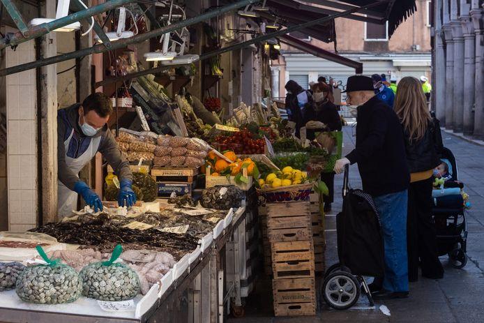 Mensen kopen groenten op een markt in Venetië, Italië.