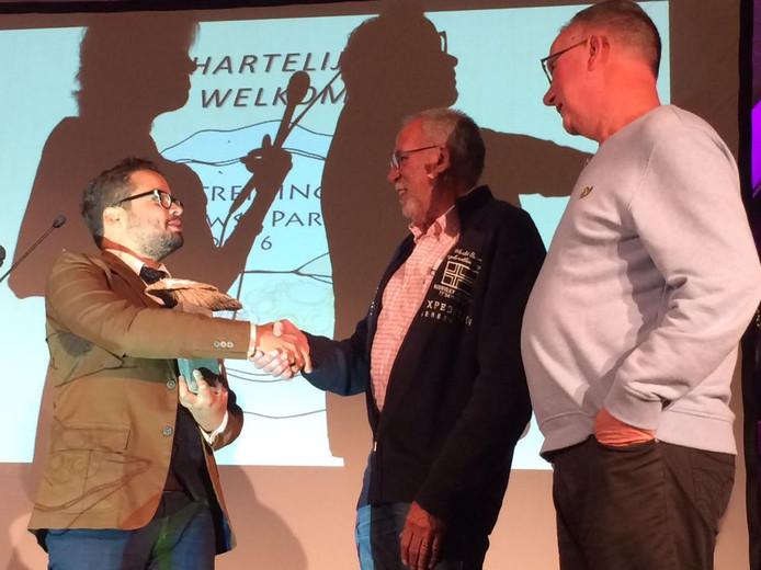 Stefano la Heijne van het LHTB Netwerk overhandigt de Zeeuwse Parel aan Lammert Veenhuizen, een van de acht Zeeuwse Roze 50+ambassadeurs.