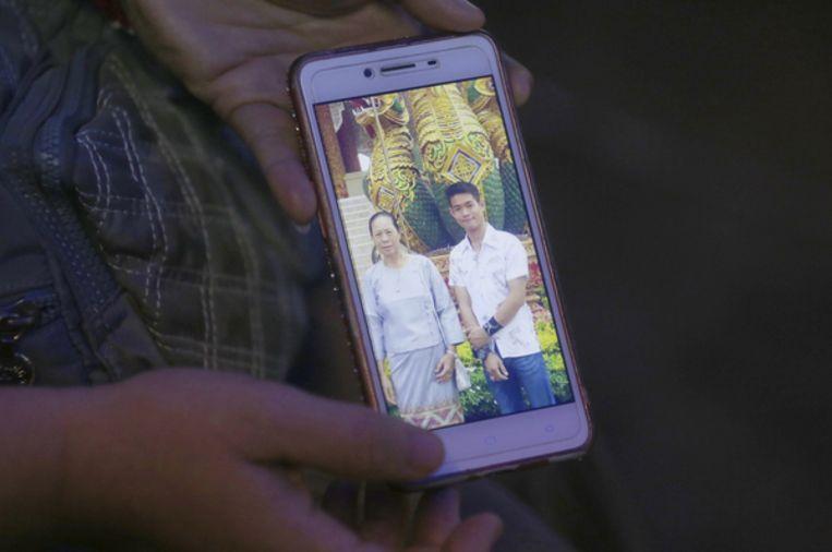 De tante van Coach Ekapol Chantawong laat een foto zien van de coach en zijn oma op een mobiele telefoon.
