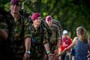 Een jonge toeschouwer geeft een Nederlandse soldaat een bemoedigend klapje.