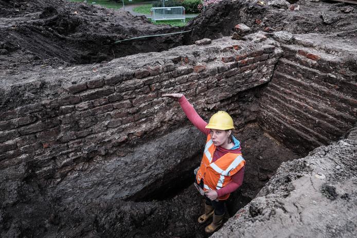Archeologe Renske den Boer bij een deel van de oude stadsmuur van Doesburg. Met achter haar de fundering van een oude waltoren.