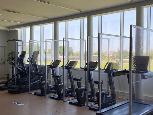 Tussen de fitnesstoestellen in Sportoase staan schermen.
