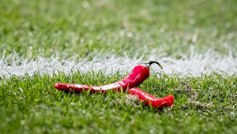 Supporters gooien rode pepers op het veld als protest. Beeld Proshots