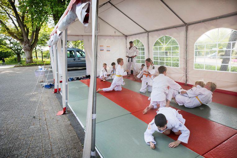 Kinderen die buiten onder een partytent judotraining krijgen bij Van Diermen Sport. Beeld Werry Crone