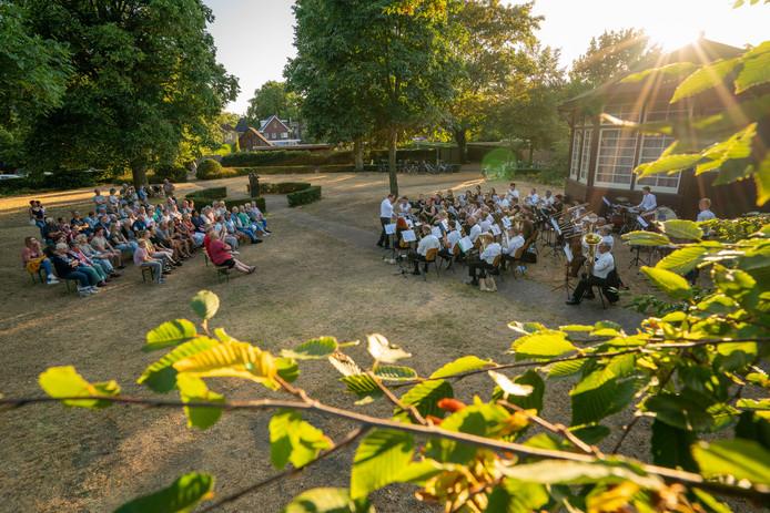Het publiek geniet met volle teugen van het eerste van twee  buitenconcerten van de Hellendoornse Harmonie in park De Geuren.