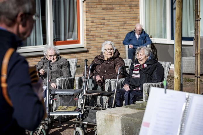 Zanger en accordeonist Wim Oldebeuving treedt op in de tuin aan de voorzijde van woonzorgcentrum Het Dijkhuis. Hij mag nu niet binnen optreden.