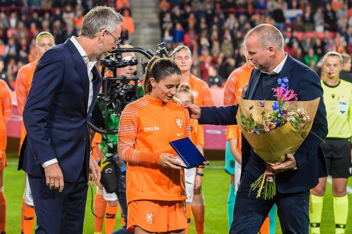 Daniëlle van de Donk neemt de felicitaties en geschenken in ontvangst van KNVB-directeuren Jan Dirk van der Zee (links), en  Nico-Jan Hoogma (rechts).