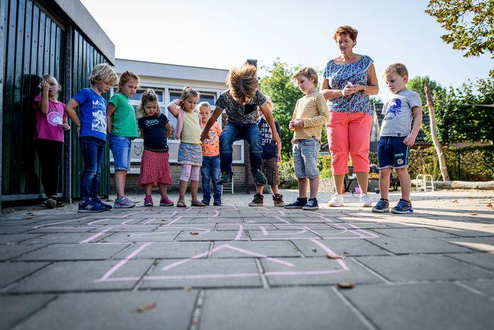 Groep 1, 2 en 3 van obs De Voshaar in Haarlo krijgt buiten op het schoolplein les in klok kijken en lezen.