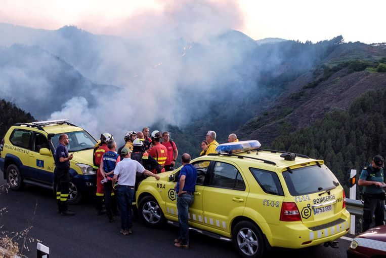 Hulpverleners en brandweermannen overleggen op Gran Canaria terwijl achter hen het vuur voortraast.