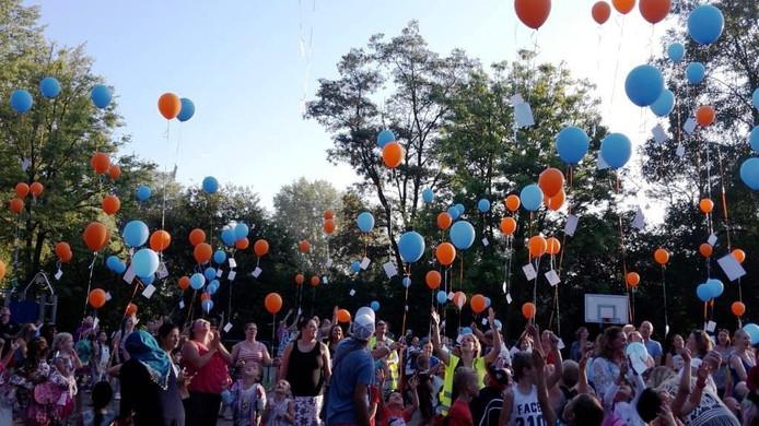 Kinderen van De Zevensprong laten ballonnen op.