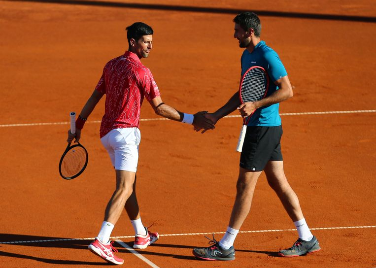 Een ouderwetse handdruk tussen Novak Djokovic en Marin Cilic tijdens het nu beruchte tennistoernooi in Kroatië. Beeld REUTERS