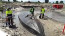 Als een gestrande walvis ligt een middeleeuwse platbodem omgekeerd in het zand. Op de plek waar hij ooit is vergaan.