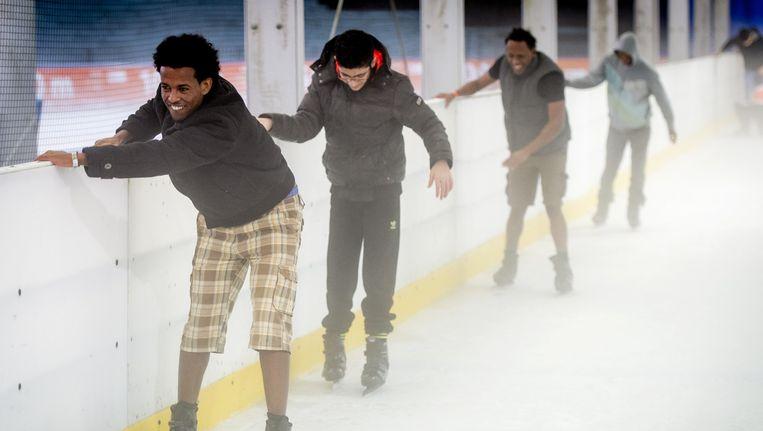 Asielzoekers doen mee aan een Hollandse Koek-en-Zopie schaatsmiddag in De Uithof in Den Haag. Beeld ANP