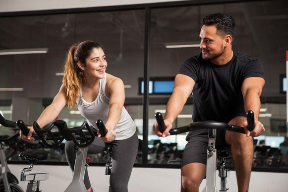 Een personal trainer in een fitnessclub samen met zijn cliënte.