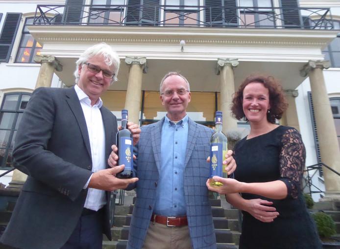 Oud-minister Henk Kamp (midden) krijgt de eerste exemplaren Royal Dutch Red & White van de wijnboeren Roelof en Ilse Visscher.