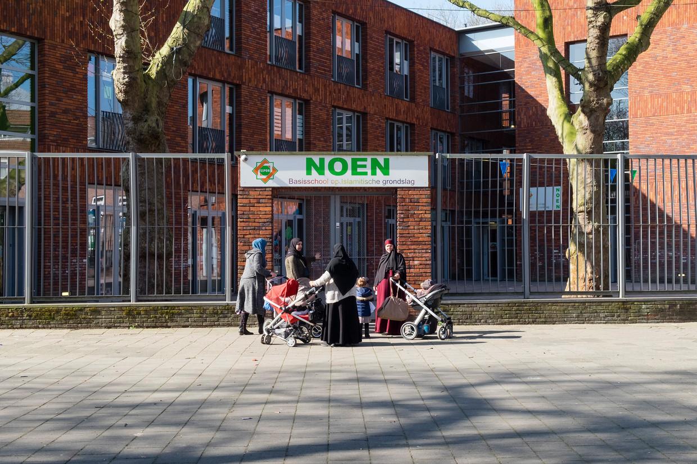 Moslimvrouwen staan voor de islamitische school Noen in de wijk Kralingen Crooswijk met elkaar te praten.