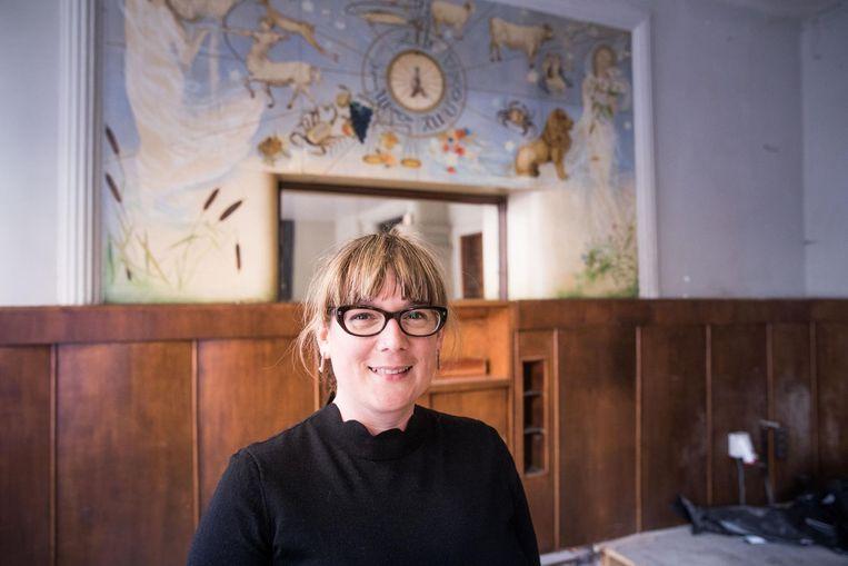 Sara bij een gerenoveerde muurschildering.