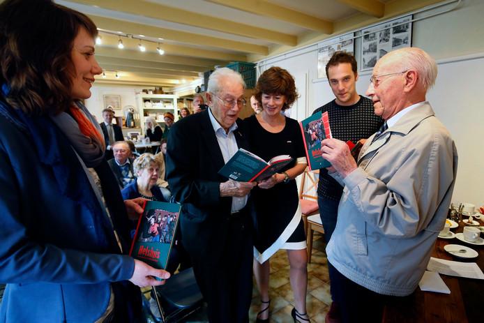 Cees Mijnster (rechts) en Marius den Breejen (midden) bekijken het zojuist overhandigde boek. Uiterst links de schrijfster Judith Brinkman.