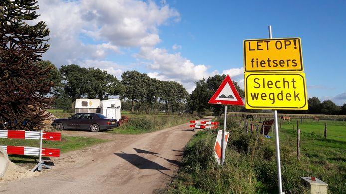 De gemeente waarschuwt voor slecht wegdek. Het stuk zandpad is noodgedwongen als doorgaande weg in gebruik.
