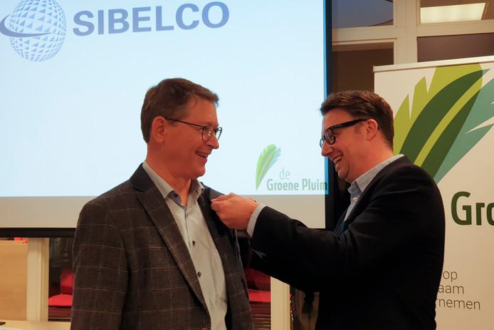 Wethouder Mike Hofkens speldt De Groene Pluim op bij Peter Jaspers, sustainability manager van Sibelco.